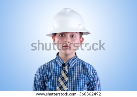 Aspiring young tween boy dreaming of becoming an engineer in hardhat and necktie with a whimsical expression - I am going to be an engineer - against a blue background - stock photo