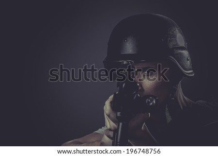 Assault, paintball sport player wearing protective helmet aiming pistol ,black armor and machine gun - stock photo