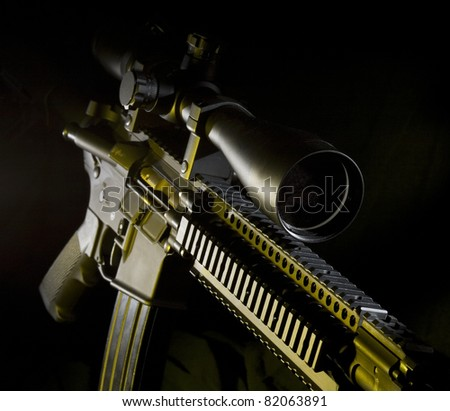 Assault rifle on a dark background with yellow side lights - stock photo