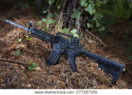 Assault rifle on pine needles with ivy and trees around - stock photo