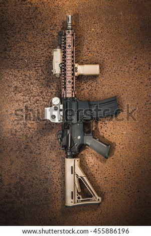 assault rifle on the rusty steel plate - stock photo