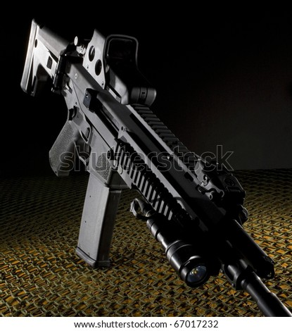 assault rifle that is black on a dark background