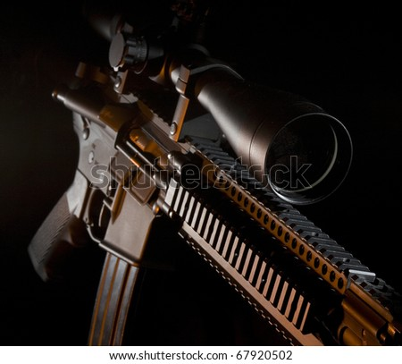 Assault weapon on a black background with an orange gel - stock photo