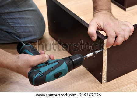 Assembling furniture from chipboard, Woodworker  screwing Chipboard screws using a cordless screwdriver. - stock photo
