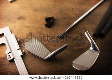 Assembling golf clubs or golf club making. Iron head, steel shaft, ferrule and grip on a well used work bench. Shot in impression-like surreal color with low key shadows. Shallow depth of field. - stock photo