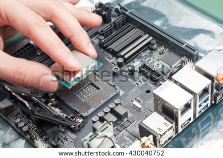 Assembling high performance personal computer, inserting CPU, processor into the motherboard socket, shallow depth of field, focus on hand - stock photo