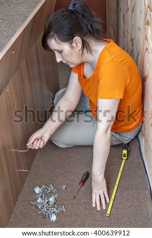 Assembling of furniture at home, woman housewife collects double bed using the hand tool, hex wrench, allen key.