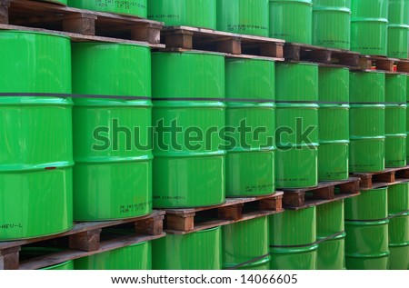 Assembly of green oil drums on wooden pallets - stock photo
