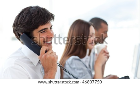 Assertive businessman talking on phone in the office - stock photo