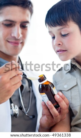 Assertive doctor giving medicine to a little boy against a white background