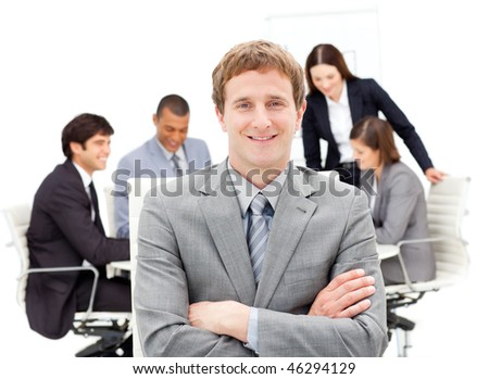 Assertive male executive with folded arms sitting in front of his team in a meeting