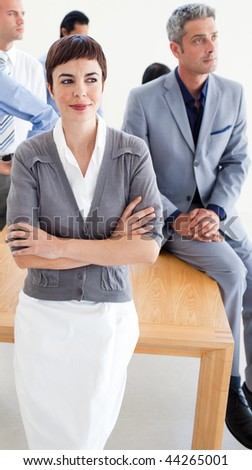 Assertive manager with folded arms in front of her team in the office
