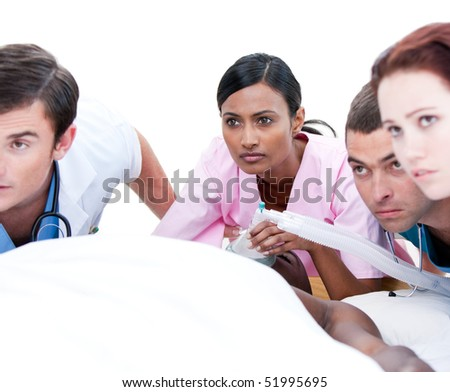 Assertive multi-ethnic medical team resuscitating a patient in a hospital - stock photo