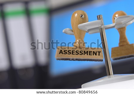 assessment marked on rubber stamp - stock photo
