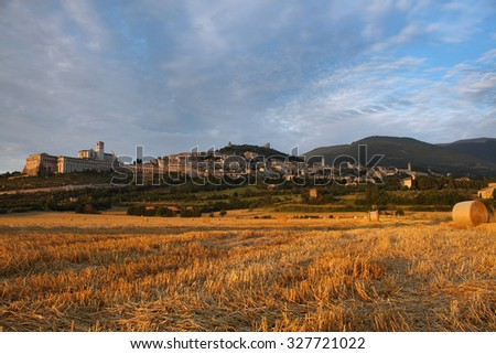 Assisi village from a hay field in sunset.