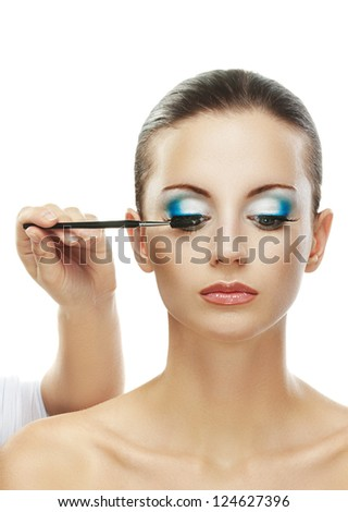 Assistant paint eyes of beautiful young woman close up, isolated on white background. - stock photo