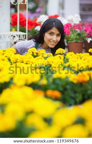 Assistant standing at a flower patch in garden center - stock photo