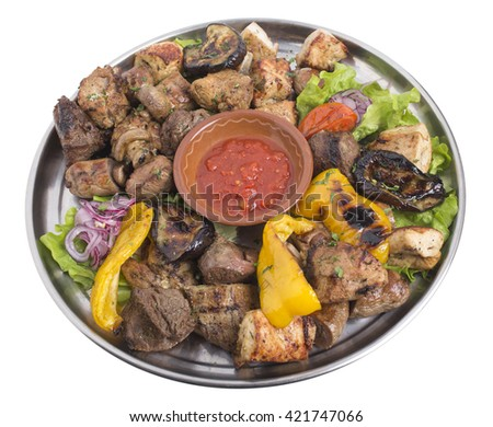 Assort of grilled meat and vegetables on a metal tray with tomato sauce. Isolated on a white background. - stock photo