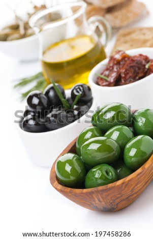 assorted antipasti - olives, pickles, olive oil, fresh rosemary and ciabatta, close-up - stock photo