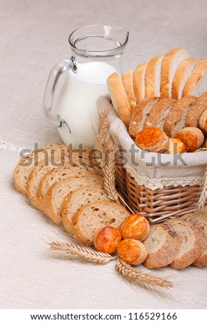 Assorted bakery products sliced, arranged in small basket. Wheat ears in front, milk jug behind - stock photo