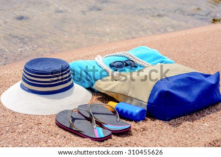 Assorted beach accessories on the sand of a tropical beach overlooking the water with a sunhat, sunscreen, towel, thongs, sunglasses and beach bag - stock photo