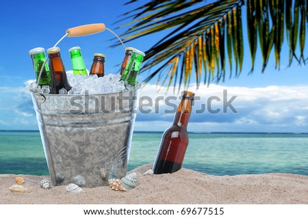 Assorted beer bottles in a bucket of ice in the sand on a tropical beach. One beer bottle without a cap is by itself stuck in the sand next to the pail. - stock photo