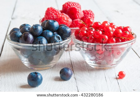 Assorted berries in glass bowls on wood: blueberry, red currant, raspberry - stock photo