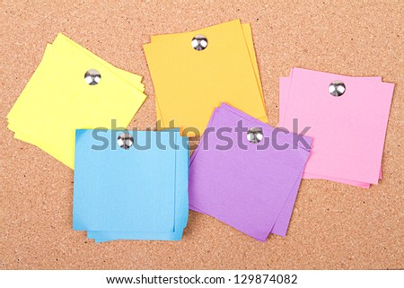 assorted blank sticky notes on a bulletin board - stock photo