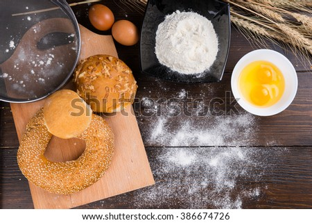 Assorted bread rolls with baking ingredients including eggs and flour in bowls viewed overhead on a wooden table with ears of wheat - stock photo