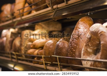 Assorted breads in stacked in a shelf in a market/bakery