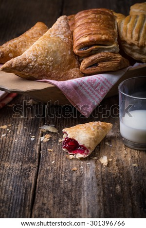 assorted breakfast pastries with jam and milk on old wooden table