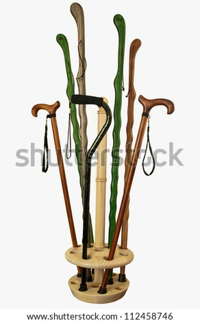 assorted canes and walking sticks in a wooden holder - stock photo