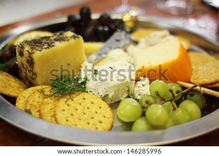 Assorted cheeses and snacks on a tray. - stock photo
