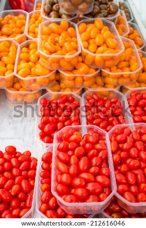 Assorted cherry tomatoes on display on a street market stall - stock photo