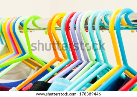 Assorted child's clothes on colorful plastic hangers - stock photo