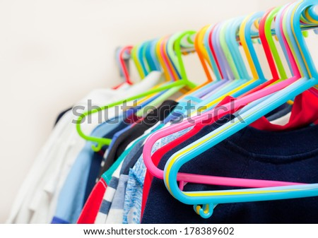 Assorted child's clothes on colorful plastic hangers