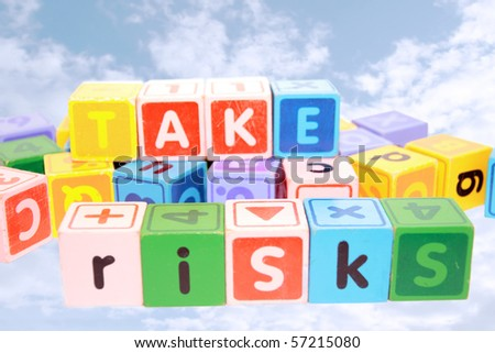 assorted childrens toy letter building blocks against a loudy background that spell take risks - stock photo