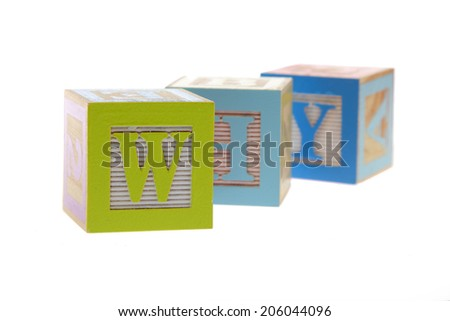 Assorted childrens toy letter building blocks against a white background/Childrens alphabet blocks spelling the words why - stock photo