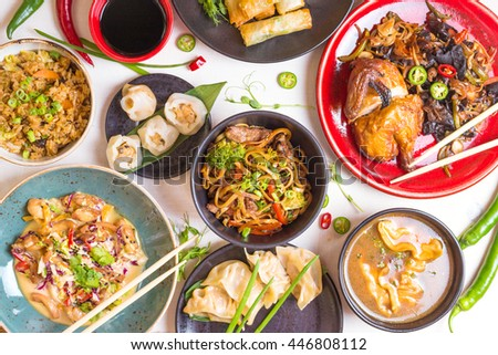 Assorted Chinese food set. Chinese noodles, fried rice, dumplings, peking duck, dim sum, spring rolls. Famous Chinese cuisine dishes on white table. Top view. Chinese restaurant concept. Asian style  - stock photo