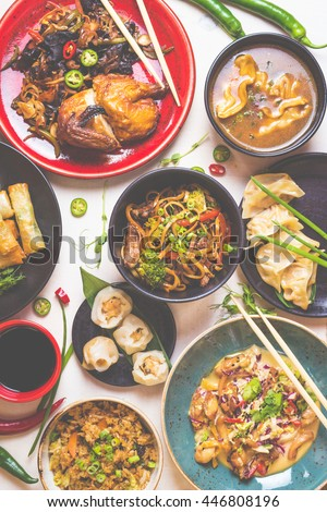 Assorted Chinese food set. Chinese noodles, fried rice, dumplings, peking duck, dim sum, spring rolls. Famous Chinese cuisine dishes on white table. Top view. Chinese restaurant concept. Toned image