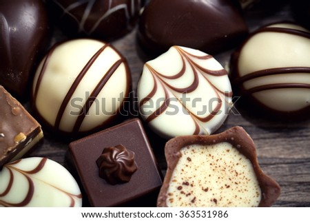 Assorted chocolate pralines on a wooden background