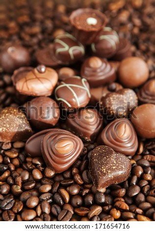 Assorted chocolate pralines on coffee beans background, selective focus - stock photo
