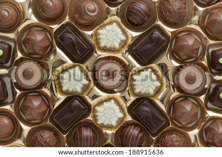 assorted chocolates confectionery in their gold box packaging - stock photo