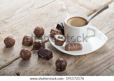 assorted chocolates confectionery with cup of coffee - stock photo