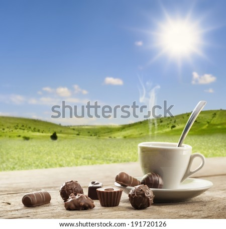 assorted chocolates confectionery with cup of coffee in sunny landscape - stock photo