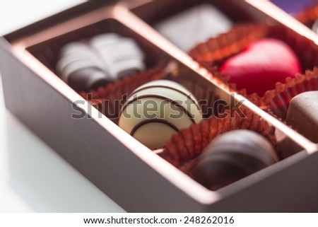 Assorted chocolates in brown box, shallow depth of field - stock photo