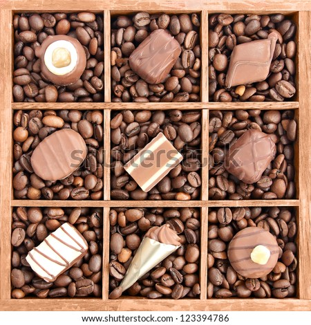 Assorted chocolates in wooden box with coffee beans (manual focus) - stock photo