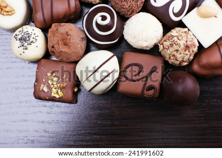 Assorted chocolates on the dark wooden smooth background - stock photo