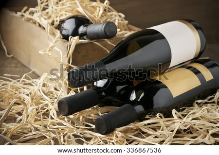 Assorted closed wine bottles lying on straw and vintage wooden box. - stock photo