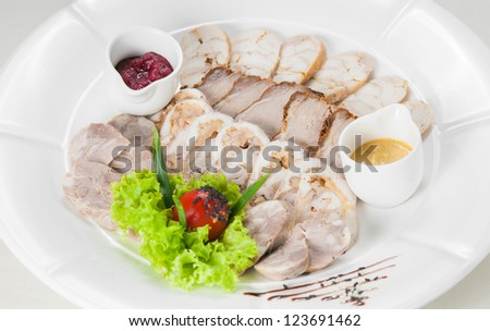 Assorted cold cuts (ham, sirloin, headcheese) with sauce, decorated with lettuce, cherry tomatoes - stock photo